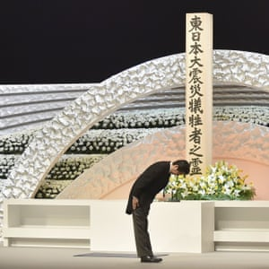 At the national memorial service in Tokyo, Japan's prime minister Shinzo Abe bows to Emperor Akihito and Empress Michiko in front of an altar for the victims.