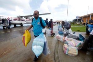 A Trinidad and Tobago immigration officer carries supplies from a Caribbean Airlines relief flight