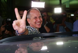 Al-Jazeera journalist Peter Greste gives a peace sign upon his arrival at Brisbane's international airport in the early hours of 5 February following his release from an Egyptian jail where he was held for more than 400 days.