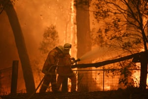 Firefighters protect a home threatened by the Gospers Mountain fire