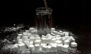A cola drink surrounded by sugar cubes