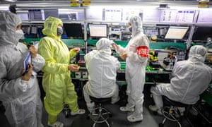 Security employees on duty check their colleagues' temperature at their workstations in Appotronics factory in Shenzhen, Guangdong province, China, 05 March 2020.