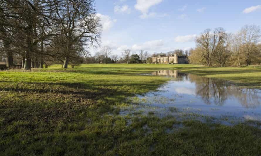 Lacock Abbey in Wiltshire, reflected in flood water in the grounds. The National Trust said climate change is affecting its properties and collections.