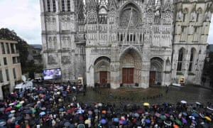 People watch the funeral service from outside the cathedral