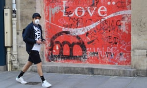 """A man wearing a protective mask walks past a mural with word """"love"""" during the lockdown in Paris"""