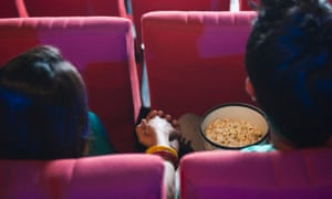 Couple holding hands in a cinema