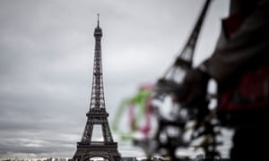 A man selling souvenirs stands in front of the Eiffel Tower in Paris.