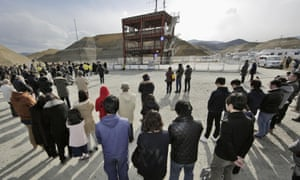 People gather in front of the skeletal remains of the disaster prevention centre in Minamisanriku