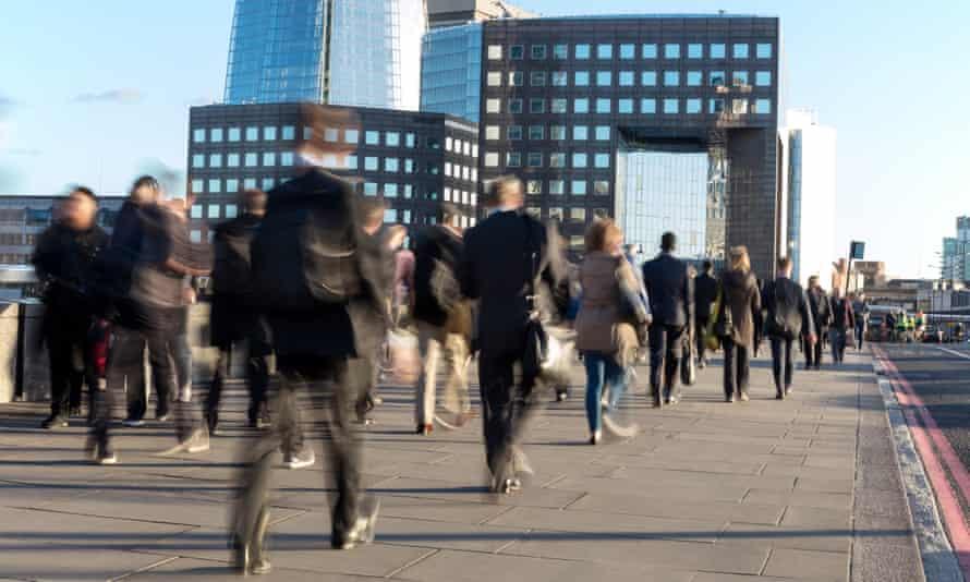 Workers walk across London Bridge.
