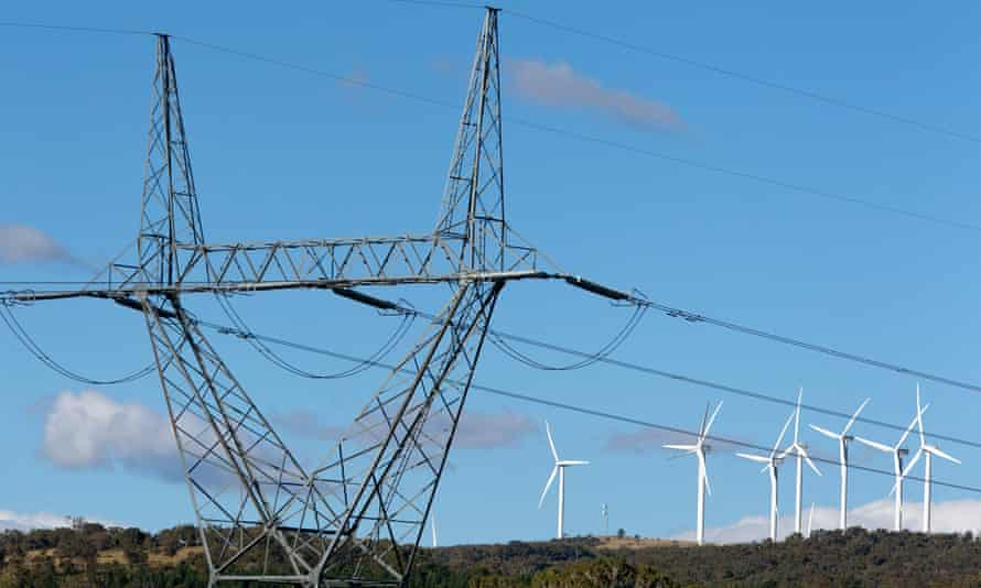 High tension power lines standing near wind turbines