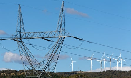 High tension power lines stand near the wind turbines
