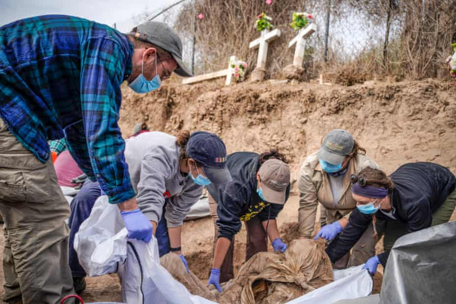 Texas State University graduate students lift the remains of a migrant from a gravesite at La Grulla cemetery on December 17, 2019 as part of the project Operation Identification.