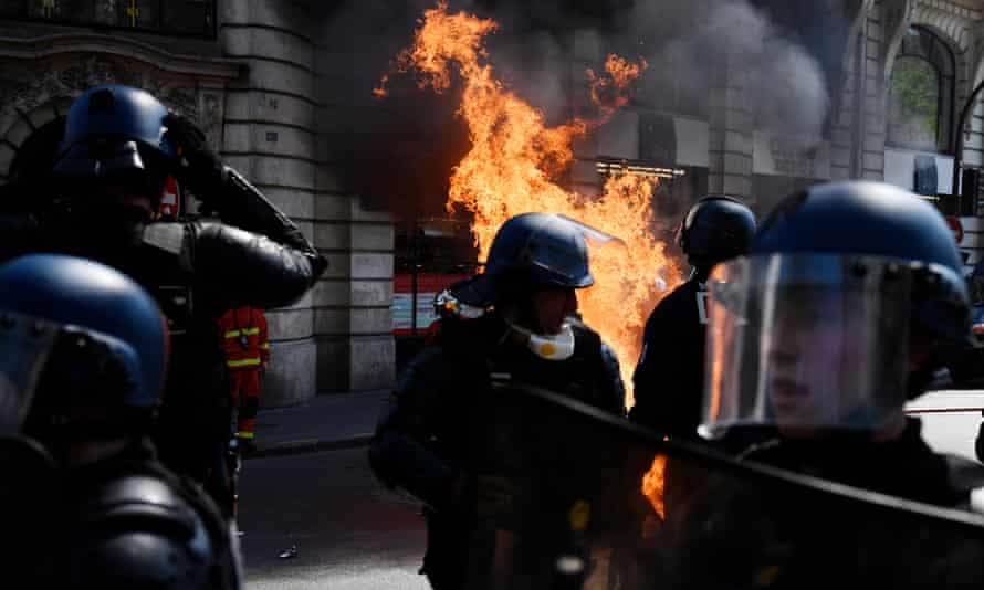 Riot police fire teargas at protesters.