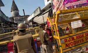 A police officer checks identity papers at a security barricade in Ayodhya