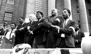 James Baldwin, on the right, joins hands with other civil rights leaders as they sing during the closing of memorial ceremonies in New York, on 22 September 1963, for the four girls killed in the bombing of the 16th Street Baptist Church in Birmingham, Alabama.