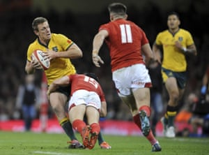 Australia's Dane Haylett-Petty looks for support as he is tackled by Wales Leigh Halfpenny.