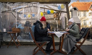 An older couple eat dinner while keeping distance from the rest of their family on 18 April in Ostersund, Sweden.