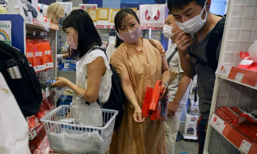 People shop at an official Olympics merchandise shop in Tokyo