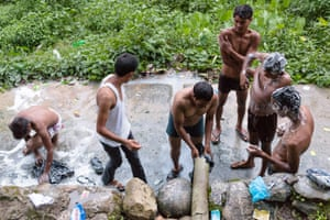 Late in the evening men gather at a spring for their daily bathing.