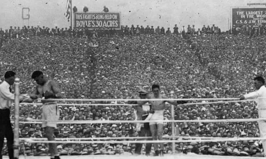 A huge crowd watches as Jack Dempsey (left) and Georges Carpentier rest between rounds of their world heavyweight tile fight in 1921.