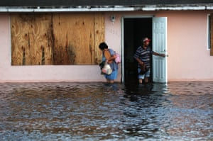 A couple leave their flooded home the morning after Hurricane Irma swept through the area in September 2017 in Fort Myers, Florida.