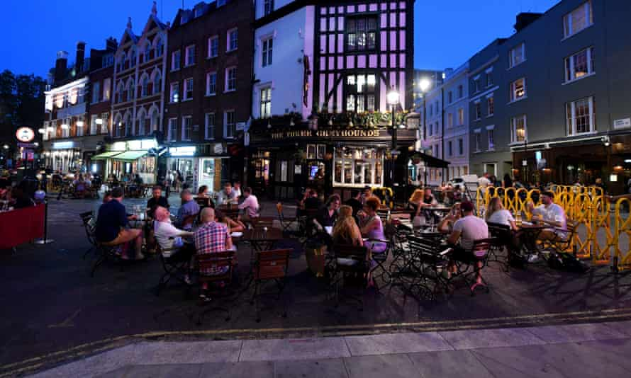 Outdoor tables full of people in a Soho street