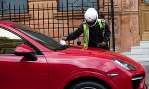 A traffic warden gives a parking ticket to a Porsche in London. The US embassy alone has amassed over £10m in unpaid congestion charges in the capital since 2003.