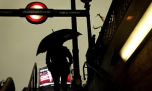 A person exits a London Underground station in heavy rain