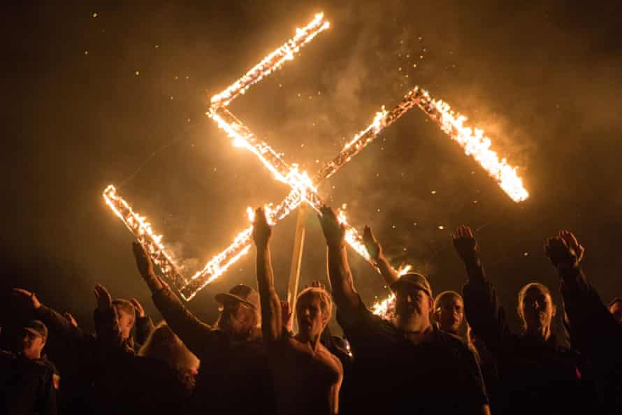 Supporters of the National Socialist Movement, a white nationalist political group, give Nazi salutes while taking part in a swastika burning in Georgia on 21 April 2018.