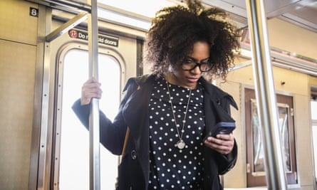 A young woman using her phone on the train