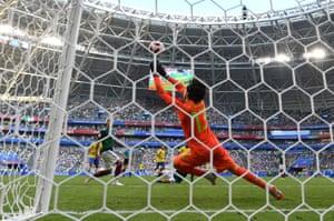 Mexicos keeper Guillermo Ochoa paws away Paulinho's shot.
