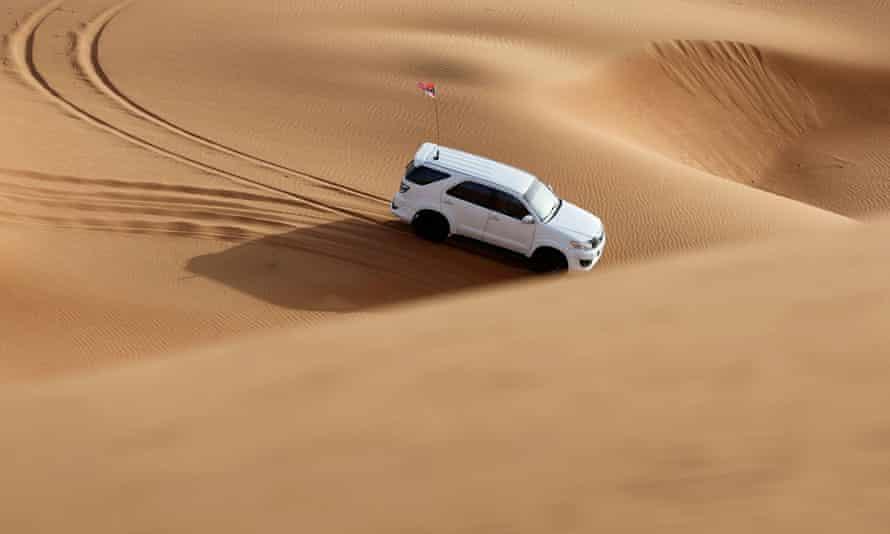 A man drives his car in the desert near Sharjah, United Arab Emirates, June 25, 2021.