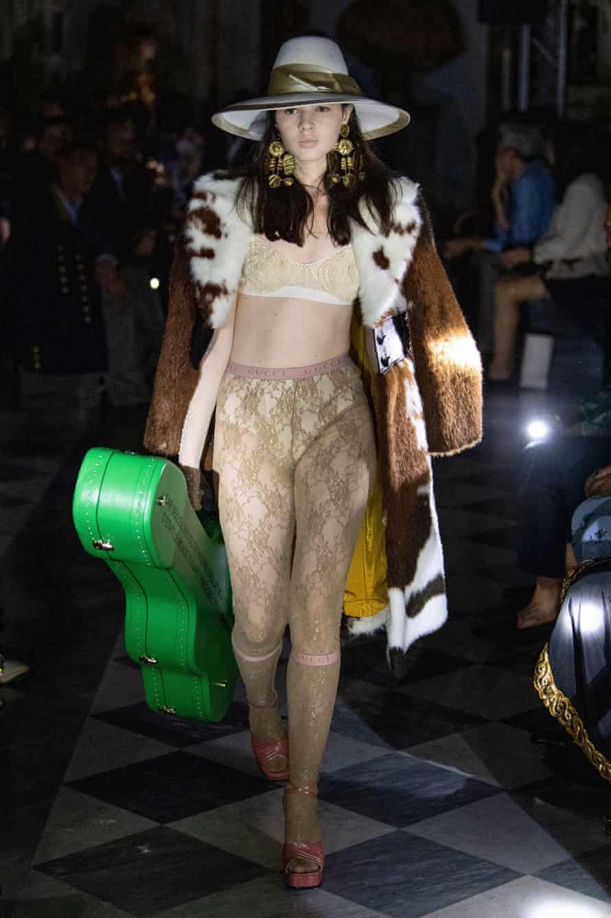 A model carries a 'Gucci band' guitar case.