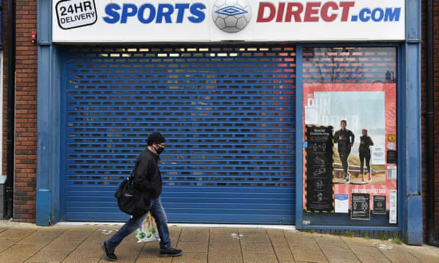 A man walks past a Sports Direct store