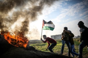 A man waves a Palestinian flag during clashes with Israeli soldiers
