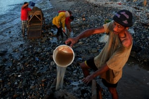 A family digs and sifts sand to look for gold