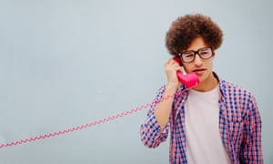Portrait of young man talking on vintage telephone