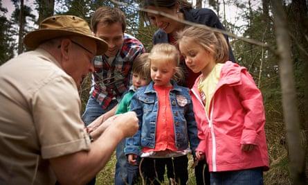 Ranger and children inspecting forest life