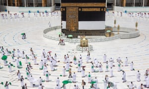 People stand near the Kaaba at the almost empty Grand Mosque in Saudi Arabia's holy city of Mecca