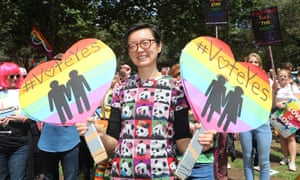 A supporter of marriage equality holds signs at a rally in Sydney encouraging people to vote yes in the postal survey. The results will be known on 15 November.