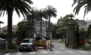 A construction workers stands in front of the Presidio Terrace, a gated community in San Francisco.