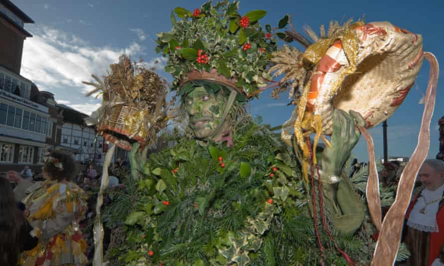 The Holly Man holds up the crowns for King Bean and Queen Pea, Bankside, London