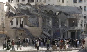 People gather outside a house destroyed by an airstrike in Sana'a