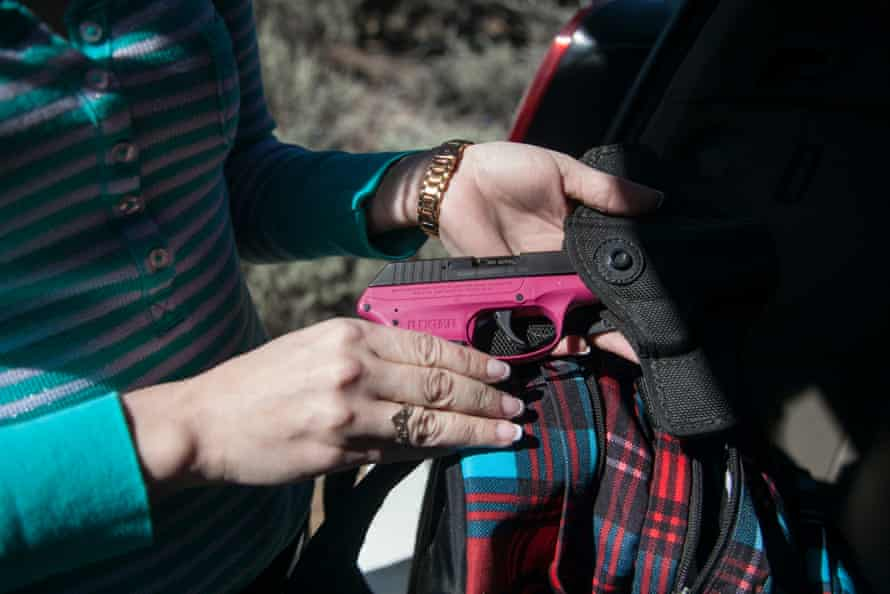 Sacha Johnston displays the gun she takes with her outdoors.