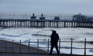 A man walks along the Brighton seafront on a dark and blustery day.