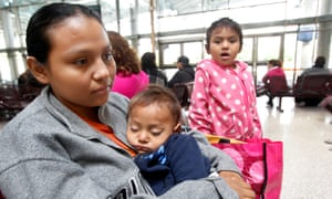 Gabriela Mata, 21, of El Salvador holds her one-year-old son, along with her four-year-old daughter, while they wait to take the bus at the McAllen Central Bus Station on 2 December 2016.
