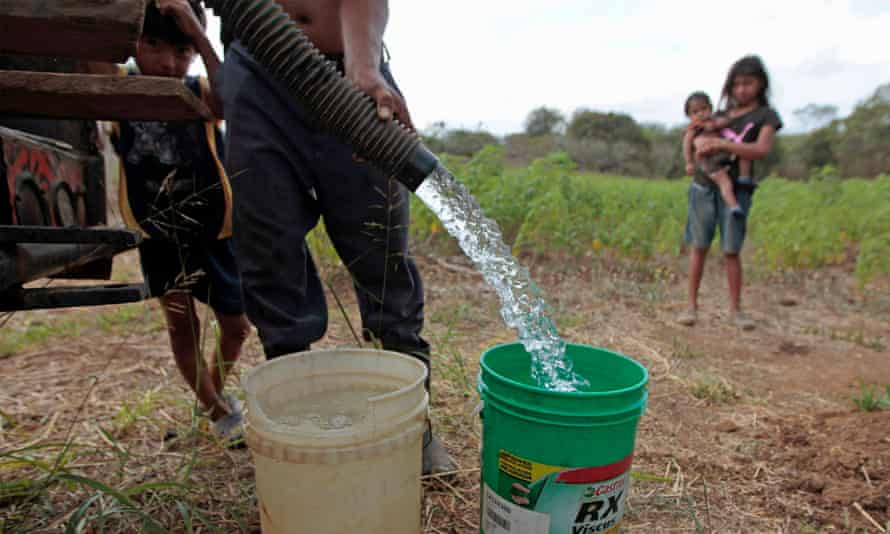 A man from the indigenous community of Pacayita collects water to irrigate a papaya field in Masaya, Nicaragua.