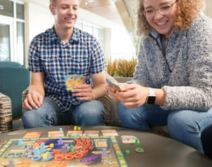 a young man and young woman play the board game cytosis