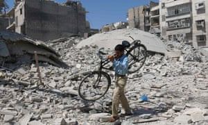 A Syrian man carries a bicycle through rubble