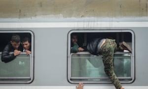 Refugees clamber aboard a train in Croatia